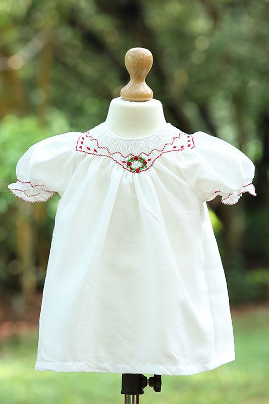 Bishop smocked Dupiol dress with bullion christmas wreath in red and white. The fabric is faux silk and is available in red and white color.