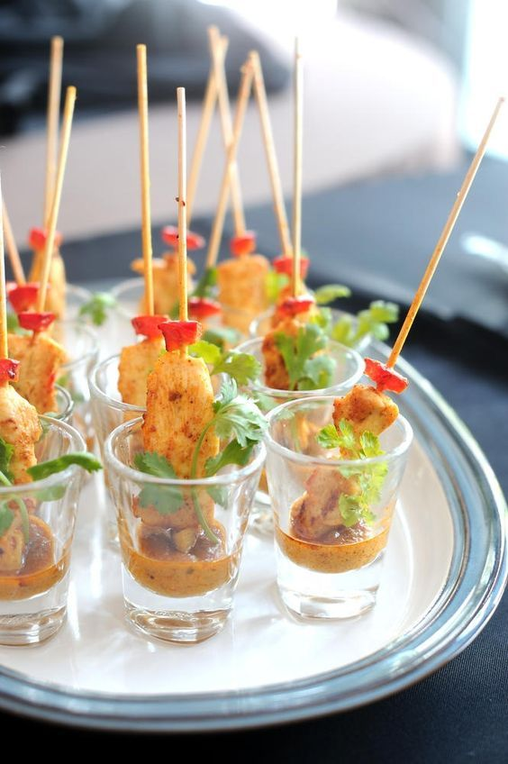 Chicken satay appetizers served in a shot glass. Or anything served like this, makes it easy.