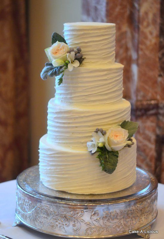 Simple 2-tier cake with rippled white icing and 2 decorative flowers | 10 Buttercream Wedding Cakes We'd (Almost) Kill For