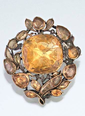 An early 18th century citrine, topaz and diamond brooch  The large central cushion shaped citrine within an topaz openwork floral surround, with rose-cut diamond point detail, mounted in silver with coloured foil backs