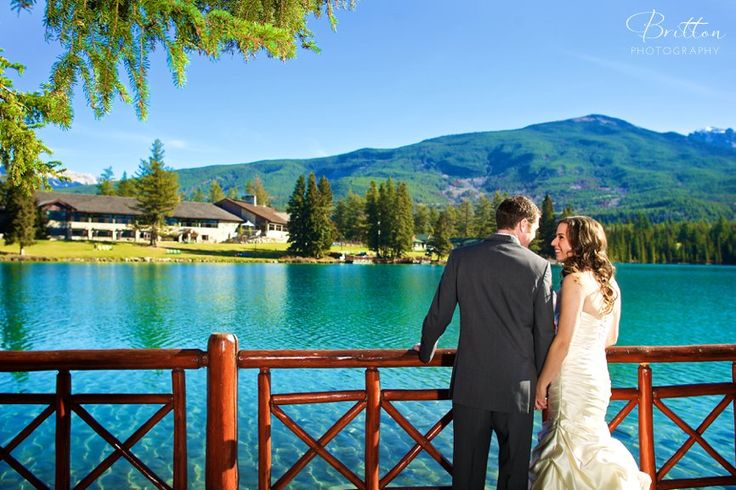 The bride and groom sharing a special moment by the lake in Jasper, Alberta. Photo by Britton Photography.
