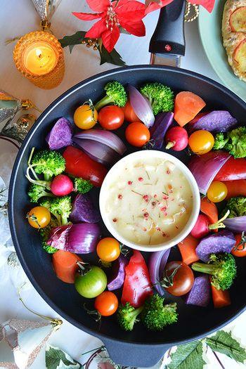 【チーズバーニャフォンデュとカラフル温&焼き野菜リース】 フライパンに盛り付け、バーニャカウダの素にパルミジャーノを加えた濃厚なソースで野菜をフォンデュします。まず前半は温野菜で。後半はソースの器を取り除いて野菜を火にかけ焼き野菜に。盛り付けたときの色を想像しながら紫イモやニンジン、赤タマネギなどきれいな色の野菜をお好みで選んでみてください。