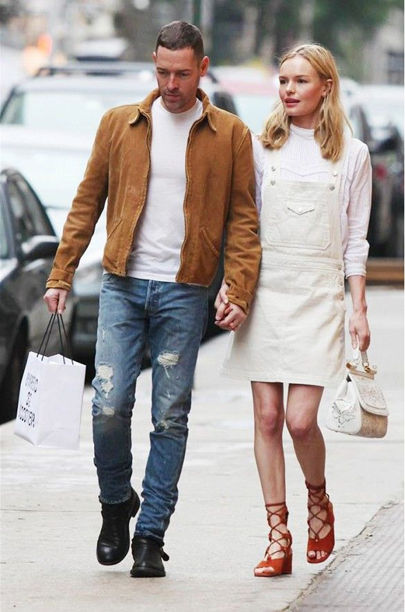 Kate Bosworth wears a white turtleneck, white overall dress, lace-up sandals, an…