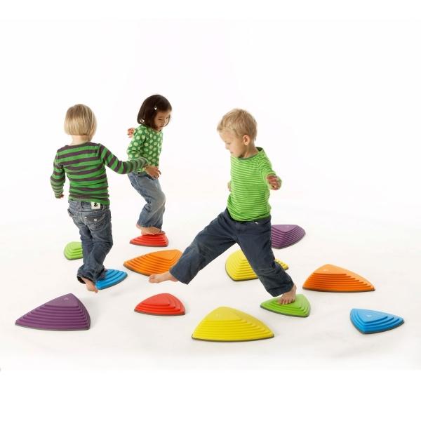 Rivierstenen: Met deze loopstenen kunnen kinderen hun coördinatie en balans ontwikkelen. De rivierstenen zijn geinspireerd door echte stenen die je tegenkomt bij wild water rivieren. De grote van de stenen varieerd. Er zijn 3 grote stenen en 3 kleine. De stenen zijn in verschillende kleuren: paars, groen, geel, oranje, blauw en rood. De uitdaging van het spel is om van de éne steen naar de ander te springen zonder de grond te raken.