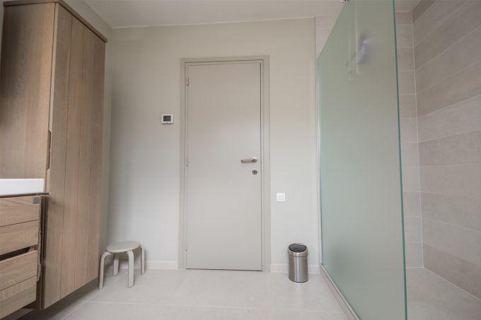Deze praktische badkamer is afgewerkt met mooie materialen. De knappe vol keramische tegels (Atlas Concorde) met hun zachte zand kleur geven een warm gevoel aan de badkamer. Het lavabomeubel uit massieve Franse eik (F&F) zorgt voor de perfecte combinatie. Bovenop de onderkast met 2 ruime lades ligt een porseleinen lavabotablet …