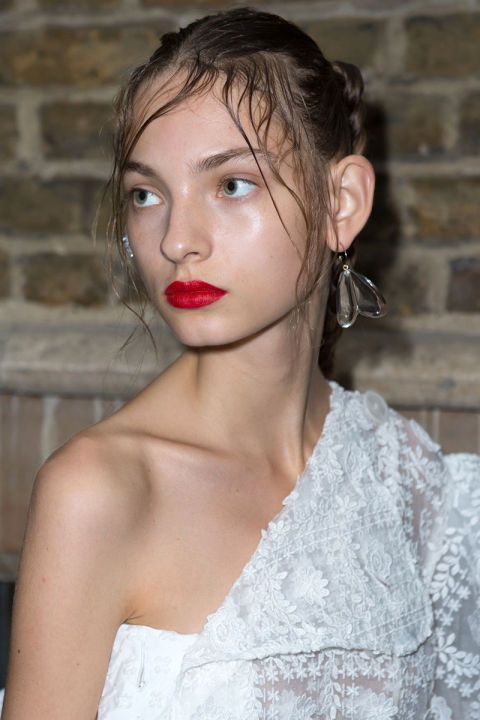 The same raw skin and red lip combination could be see backstage at Simone Rocha.