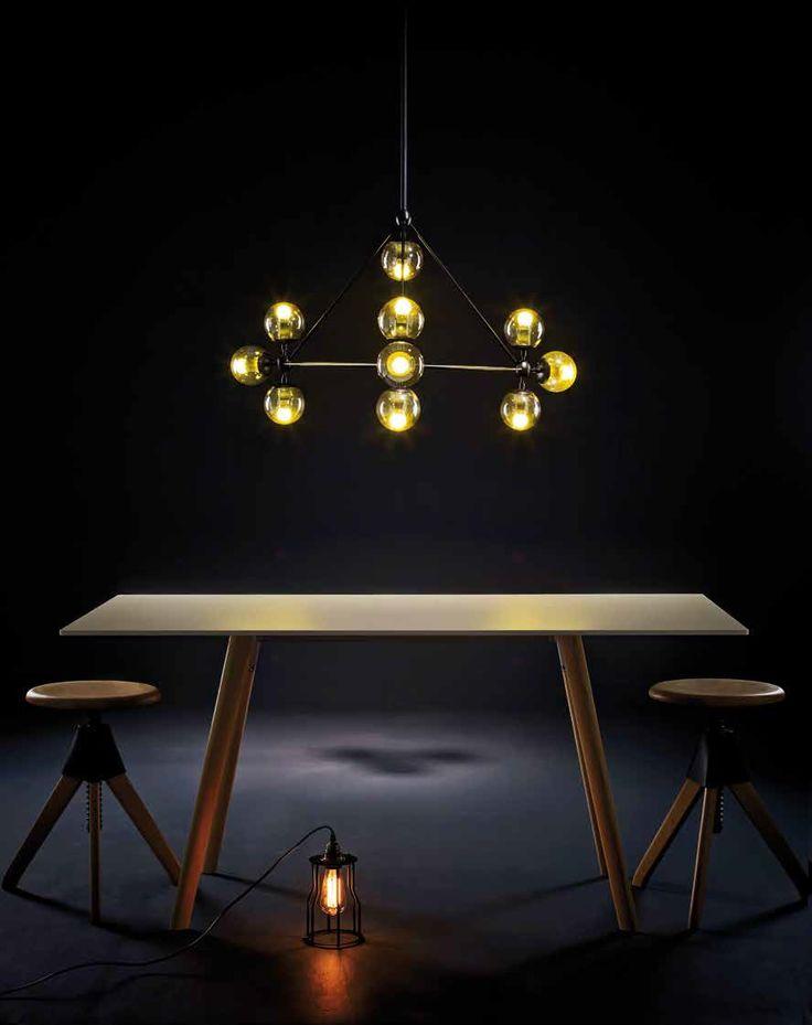 Lámpara de suspensión Diamond Chandelier, diseño de Jason Miller, en Nordic. Mesa Pilo en madera natural y blanco, y butacos Tom & Jerry, de Q Design Home. Lámpara reja metálica negra, de DeArboleda.