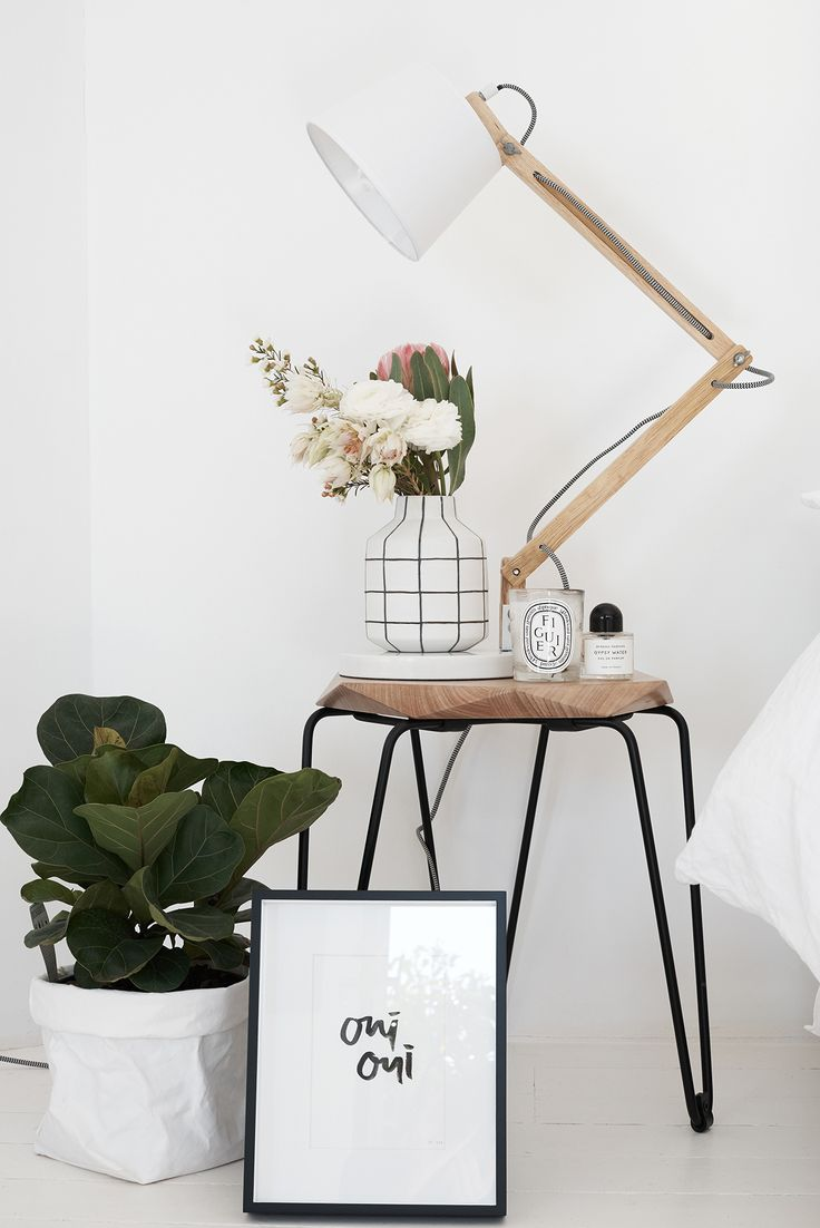 Beautiful bedroom styling. White walls Natural wood side table, plants and black and white artwork.