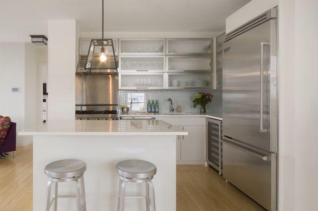 source: Spruce Interior Design website  Contemporary white kitchen design with modern cabinets, kitchen island, blue glass backsplash, Crate...