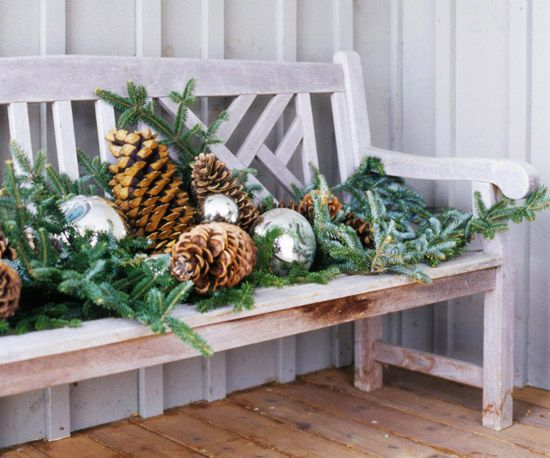 Arrange holiday greenery, pinecones, gazing balls, and ornaments on an outdoor bench.