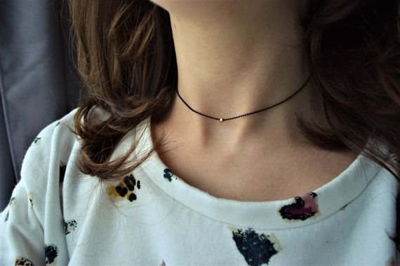 Minimalist matte black choker necklace with a 4 mm 14k gold filled bead (yellow gold or rose gold). The 1 mm ball chain is made of matte black plated brass. Solid ball chain clasp. 35 cm long. **PLEASE, MEASURE YOUR NECK SIZE before ordering and specify the right size in the order comment. ................... SUMMARY  + Matte black plated brass ball chain (1 mm) + 14k gold filled bead (4 mm) YELLOW GOLD OR ROSE GOLD. + 35 cm long - please, specify me your neck size in the order comment…
