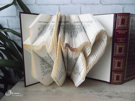 La collection A Livre Ouvert est une série de livres doccasion transformés en objets de décoration via plusieurs techniques (découpage, pliage ou décou-pliage). Chaque page est découpée et/ou pliée à la main pour donner vie à un motif.  Le modèle Mon coeur qui bat est un livre plié pour représenter le battement dun coeur. Le livre mesure 20,5 cm de haut et possède une magnifique couverture bordeaux et or. VENDU SEUL