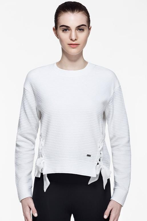 Made from a textured fabric, this lightweight style features lace-up detailing to give you customized coverage.  A relaxed design allows you to move freely, giving you an easy and comfortable fit.  With properties that wick moisture away from the skin, this is the perfect sweater to throw on post workout for your cool down.    Stylist's Notes: Wear this comfy style with your favourite pair of joggers, like our Hannah Cropped Joggers for a laid back look.
