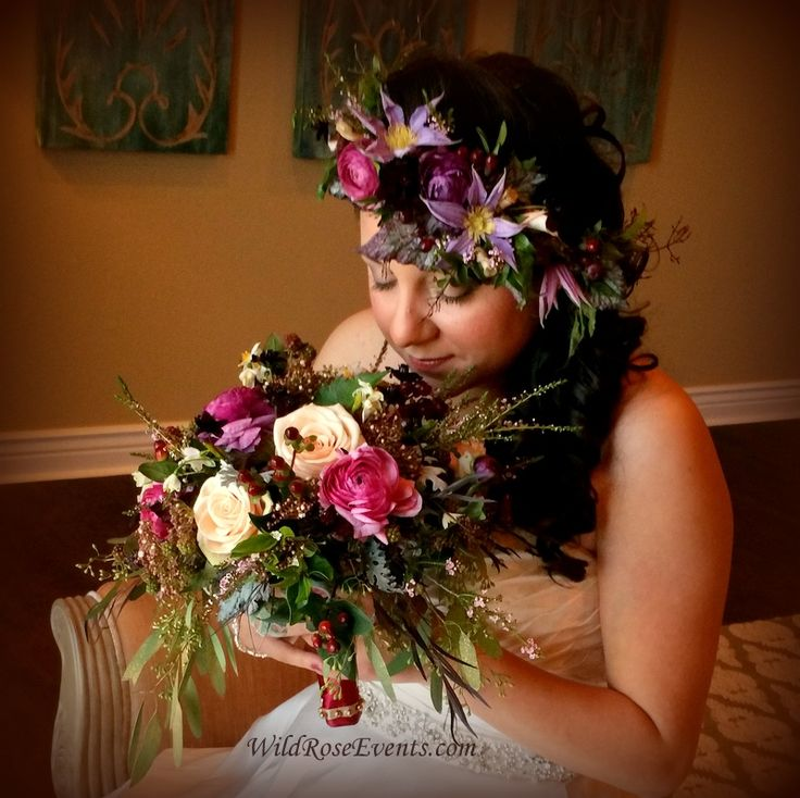 Bridal bouquet of ranunculus, lavender kale, hypericum, chocolate cosmos and green raspberries with clematis and begonia leaves in the hair flower crown. #WildRoseEvents #weddinglfowers #hairflowers #bridalbouquet