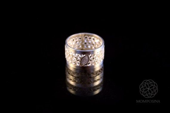 Woven silver filigree ring with traditional colonial figures.
