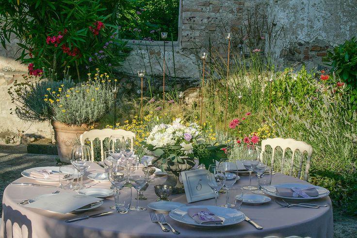 Tra i fiori coloratissimi del patio, una mise en place elegante e delicata.