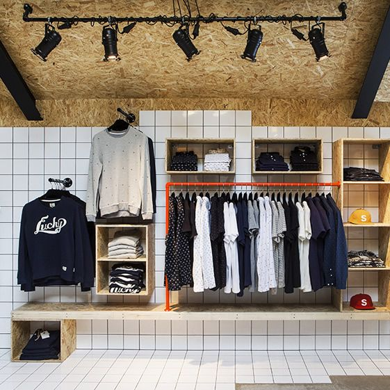 The shop has been designed by HAF Studio and the idea was to mirror the clothing brand's raw and rough character in the interior. To that end, OSB wood cladding and matte metal cage-like lattices have been paired with ceramic tiles to put a bit of gloss on proceedings...