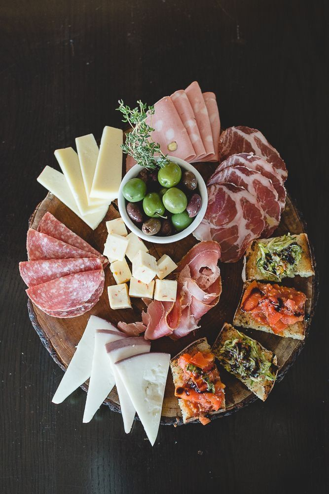 Nice Italian antipasto style meat and cheese tray, bruschetta toasts on the side.