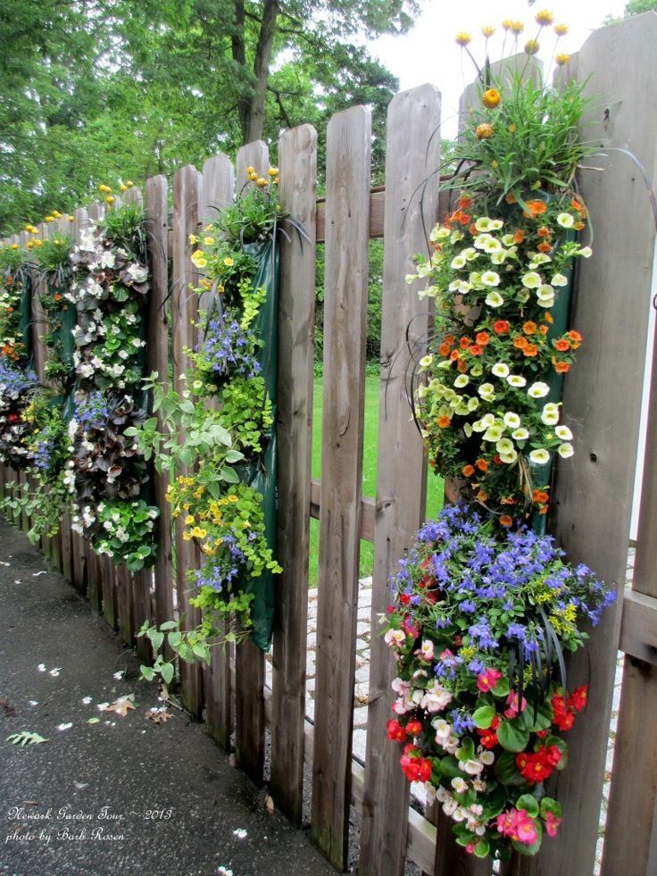 Hanging bags of annuals on fence.... like this idea since they're once a year flowers... will make it easier to clean up at the end of the summer.