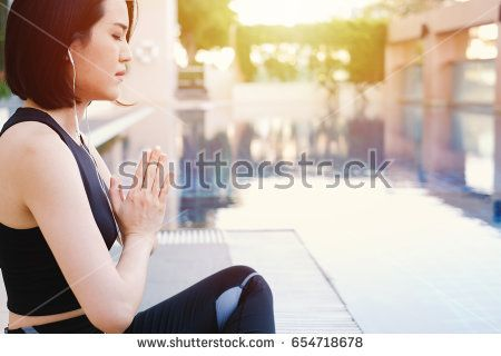 Woman meditating in the lotus position and listening music at outdoor swimming pool with copy space