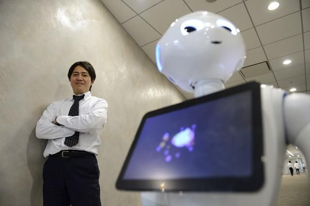 Fumihide Tomizawa, president of Softbank Robotics a unit of SoftBank Corp., poses with the company's humanoid robot Pepper following an interview in Tokyo, on Sept. 1, 2014.
