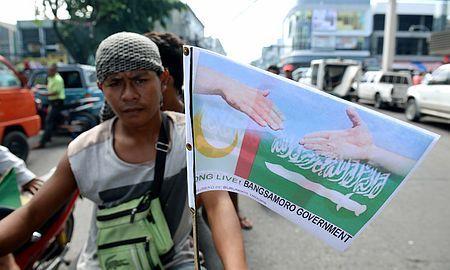 27日、フィリピン南部ミンダナオ島コタバトで、政府とイスラム武装勢力の包括和平合意を歓迎する旗を掲げる男性(AFP=時事) ▼27Mar2014時事通信|ミンダナオ包括和平に調印=政府とイスラム武装勢力-40年超の紛争に区切り・比 http://www.jiji.com/jc/zc?k=201403/2014032700857