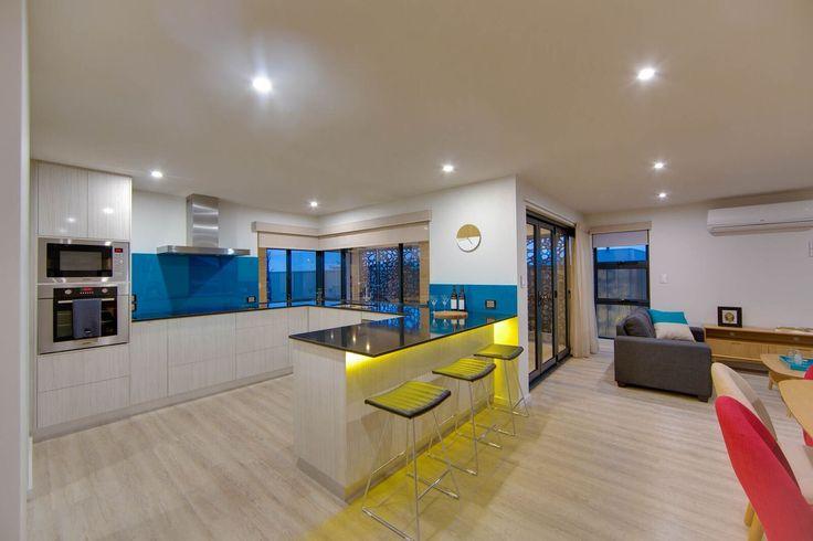 Yellow downlights underneath the breakfast bar add a modern twist to this kitchen.