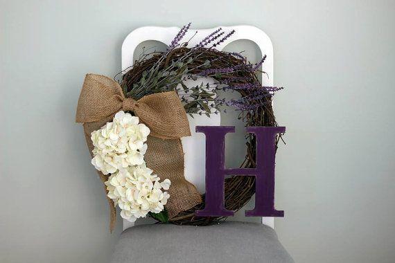 Magnifique couronne de vigne assemblé main. Comprend des fleurs de lavande et Hortensia, un arc de toile de jute et la lettre en bois. Uniquement des