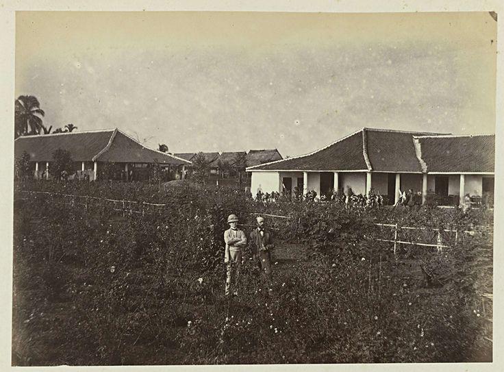 Woodbury & Page | Twee mannen voor een gebouw, Woodbury & Page, 1863 - 1869 | Twee Europese mannen poserend tussen bloemenstruiken. Achter een hek een gebouw waarvoor geweren met bepakking op de grond staan opgesteld. Onderdeel van het groene fotoalbum met foto's van Java, uit het bezit van apotheker Specht-Grijp, die in 1865 vanuit Batavia naar Nederland terugkeerde.