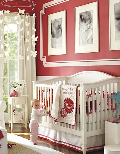 "A palette of red and white is rich and classic. Using the high-contrast crib bedding as our inspiration, we painted the walls a deep red with white trim and decorative accents. Within the painted ""gallery,"" we hung oversize black-and-white prints of favorite photos, with white frames and mats to make the images pop. White furniture and a neutral floor keep the feeling open and playful."