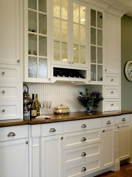 """much better idea than a full wall of """"pantry"""" cabinets...add interest with glass front cabinets and a place for display on the shallow counter top (in wood). Not a prep space so no need for marble or granite or whatever."""