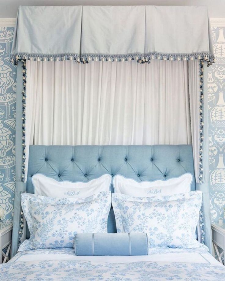 light blue traditional bedroom with canopy and tufted headboard.