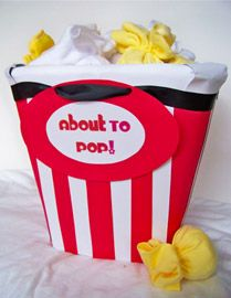 There is a basket inside the cake with a stuffed giraffe, a baby outfit, receiving blankets and burpclothes in it. There are also 20+ diapers and the popcorn is made from a dozen washcloths, a hat, two pair of mittens and three pair of socks.