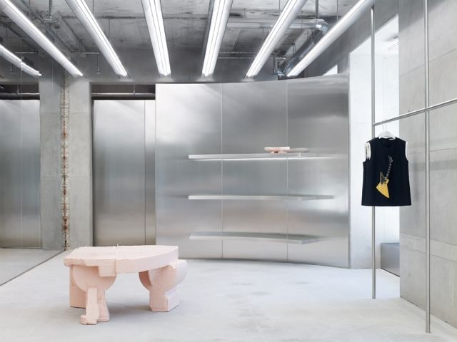 MUNICH – Becoming Swedish fashion brand Acne Studios' signature,a steel-clad store finds itself amid an urban landscape where innovation and tradition intersect.The sleek concept seen in Seoul's Gagnam shopping district, New York's SOHO district and Berlin'sPotsdamer Straße now arrives in Munich's Maximiliansplatz. The glow emanating from it's gleaming materials spills out onto the street through the building's neo-Gothic façade of large glass panes, doubling as a dynamic window display…