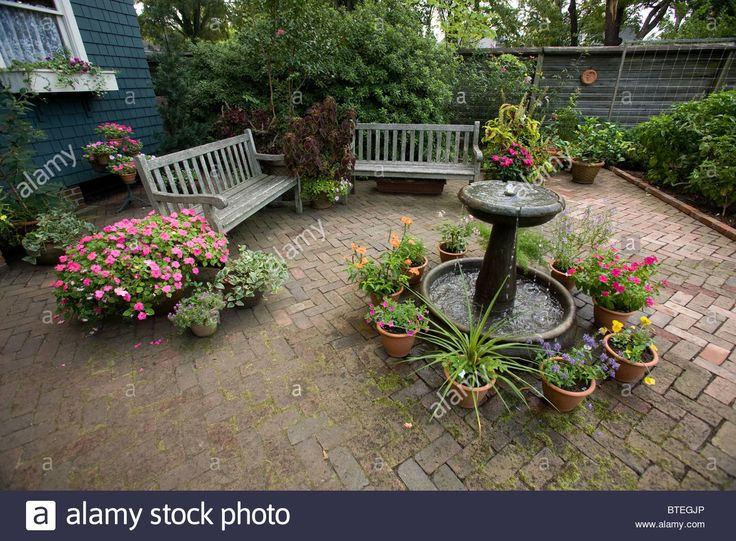 Brick courtyard with water fountain, potted plants and benches. Stock Photo