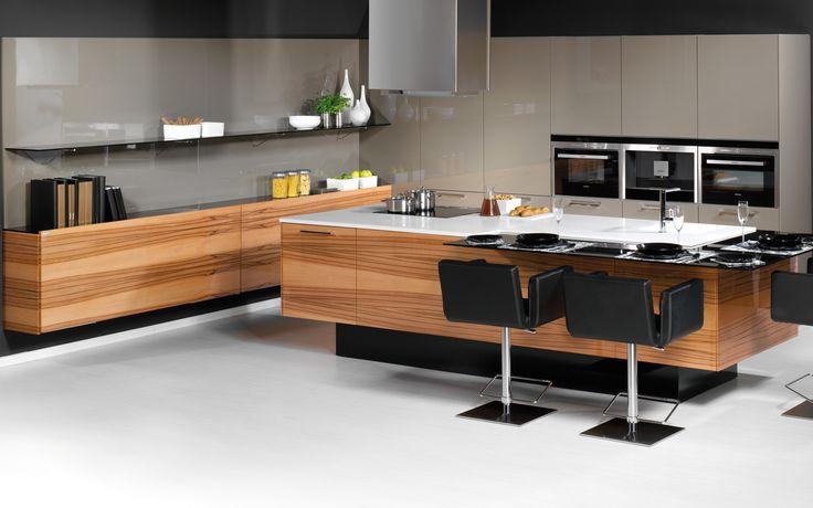 Moderní kuchyně LINE / PALOMA se skleněným barovým pultem ve tvaru L, který koresponduje se vzdušnými skleněnými policemi. Spotřebiče v technické skříni