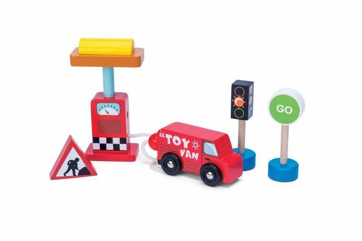 Un ensemble d'accessoires routier en bois de la marque Le toy van comprenant un petit camion, une pompe à essence et des panneaux de signalisation réversibles. Idéal pour jouer seul ou pour compléter les tapis de voiture, les garages et les circuits de train. A partir de 3 ans+