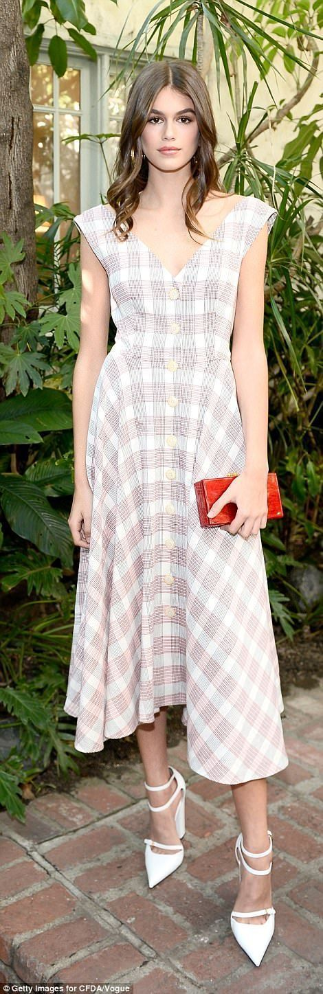 Good genes: Kaia, 16, showed off those flawless Cindy Crawford genes once again in a sleeveless plaid dress of her own, pairing with towering white ankle strap heels and a cute red box clutch #anklestrapsheelswithdress #redanklestrapsheels