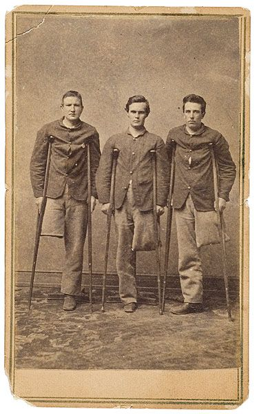 ca. 1860's, [carte de visite portrait of three young Federal soldier amputees all using hospital issue crutches. The boy at left wears a round metal identification disk pinned to his blouse], W. Snell
