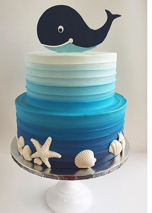 Adorable ocean themed cake with a cut-out whale on top, white chocolate sea shells and blue gradient, textured buttercream icing.