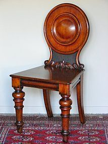 A fine Australian colonial cedar hall chair,featuring a circular bulls eye to the back raised on carved scrolls, wooden seat and large turned front legs.circa 1870. X Chantilly Antiques
