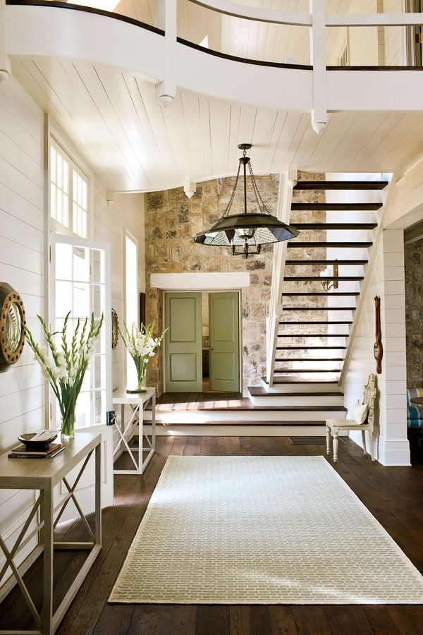 """Although the overall look and feel is traditional, Bill included a few minimalist elements for impact. """"The foyer's stairs and bridge are modern in their structural honesty,"""" says Bill. The graphic staircase adds a sculptural wow factor right inside the front door. He coated the wood-clad walls and exterior trim in glossy white paint (Benjamin Moore's Creamy White) to contrast with the rustic stone."""