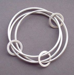 Eternity Bangle.  Hand forged from solid sterling silver made with 3 2.5mm thick round bangles and 3 moveable ring connecting them.                                                                                                                                                                                 More