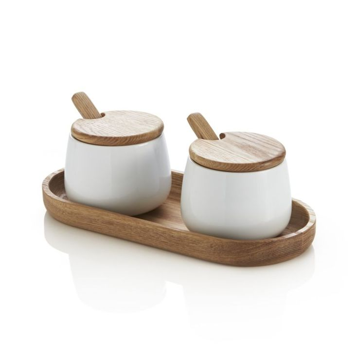 Ana Reza-Hadden's pairs porcelain and wood in a clean, warm design for condiment storage and serving.  Oval wood tray corrals two white bowls, topped with slim wooden round tops with cutouts for their adorable, round-bowled spoons. Designed by Ana Reza-HaddenAsh wood and porcelainPorcelain is dishwasher-, microwave- and oven-safeWipe clean woodFood safeMade in China.