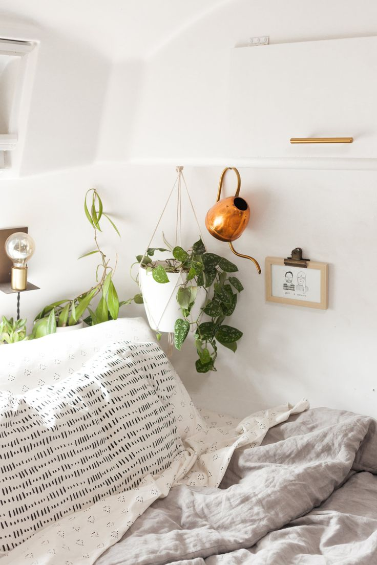 A hanging plant basks in the sunlight coming into the bedroom. The sheets and duvet cover are by Nate Berkus for Target. The sconces are by Schoolhouse Electric.
