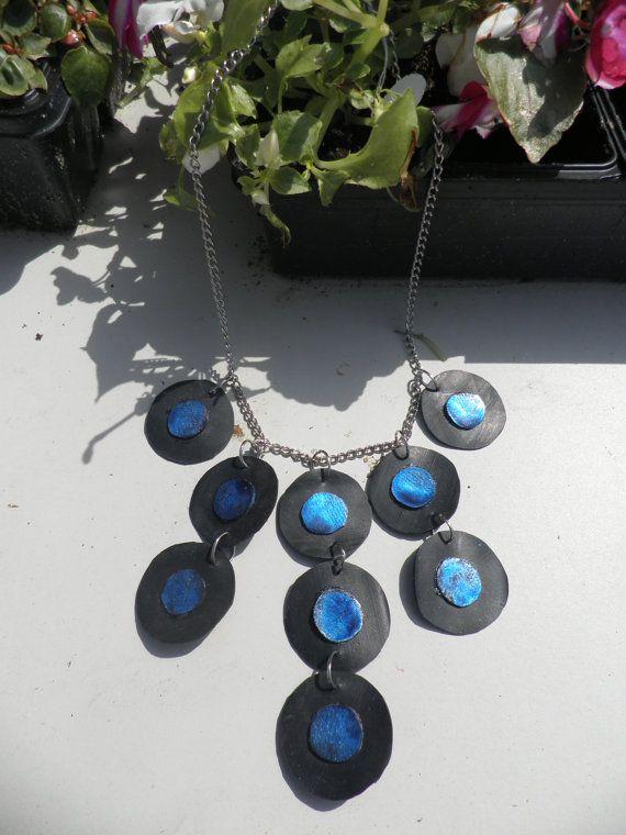 een metalen ketting en van fietsband cirkels en kleine rondjes erbovenop in mooie kleur blauw