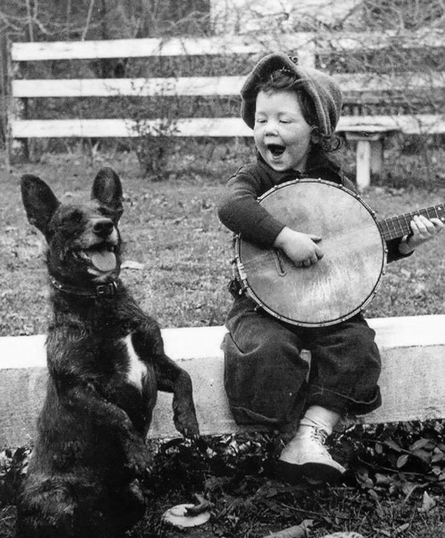 A girl playing the banjo for her dog. [Unknown]