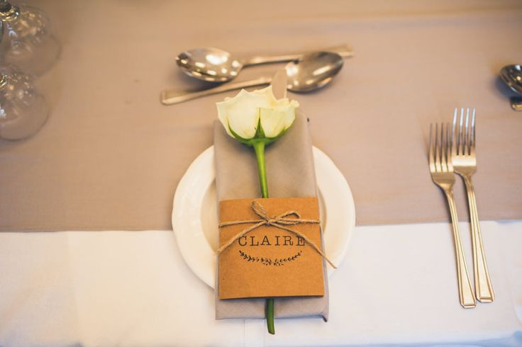 Kraft paper place names tied around the napkins with twine & decorated with a single rose stem - Image by Photography34 - A rustic styled low budget DIY wedding with outdoor venue, handmade bridal gown and handmade bridesmaid dresses. High street tweed groomsmen and dove grey colour scheme.