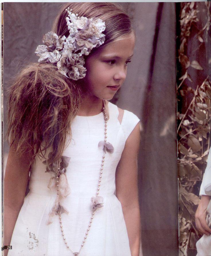 Peinado para primera comunión recogido a un lado con un adorno de flores
