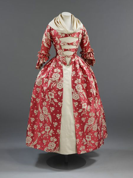 This 1760s gown features a rose-red silk with trails of ivory flowers woven in a complex technique. The fabric, a type of silk known as gros de tours, dates from the 1740s, but the gown itself has been remade into the style of the 1760s. It may have started out as a fashionable 1740s sack-back gown and would have featured the 'wing' cuff sleeve popular during that decade. In the 1760s, the garment was restyled into the popular English style of gown with pleated back.
